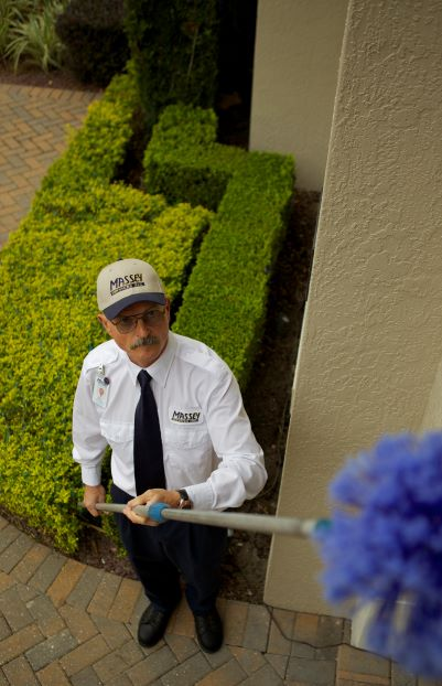 Pest Control Technician sweeping eaves for pest nests and webs.