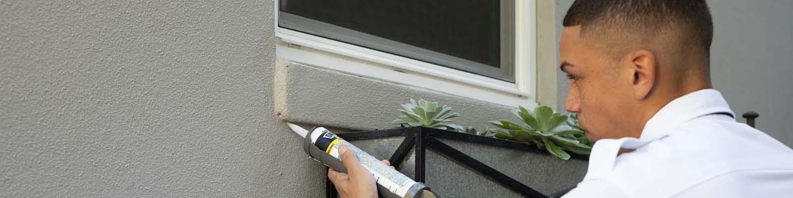 Pest Technician caulking window pane.